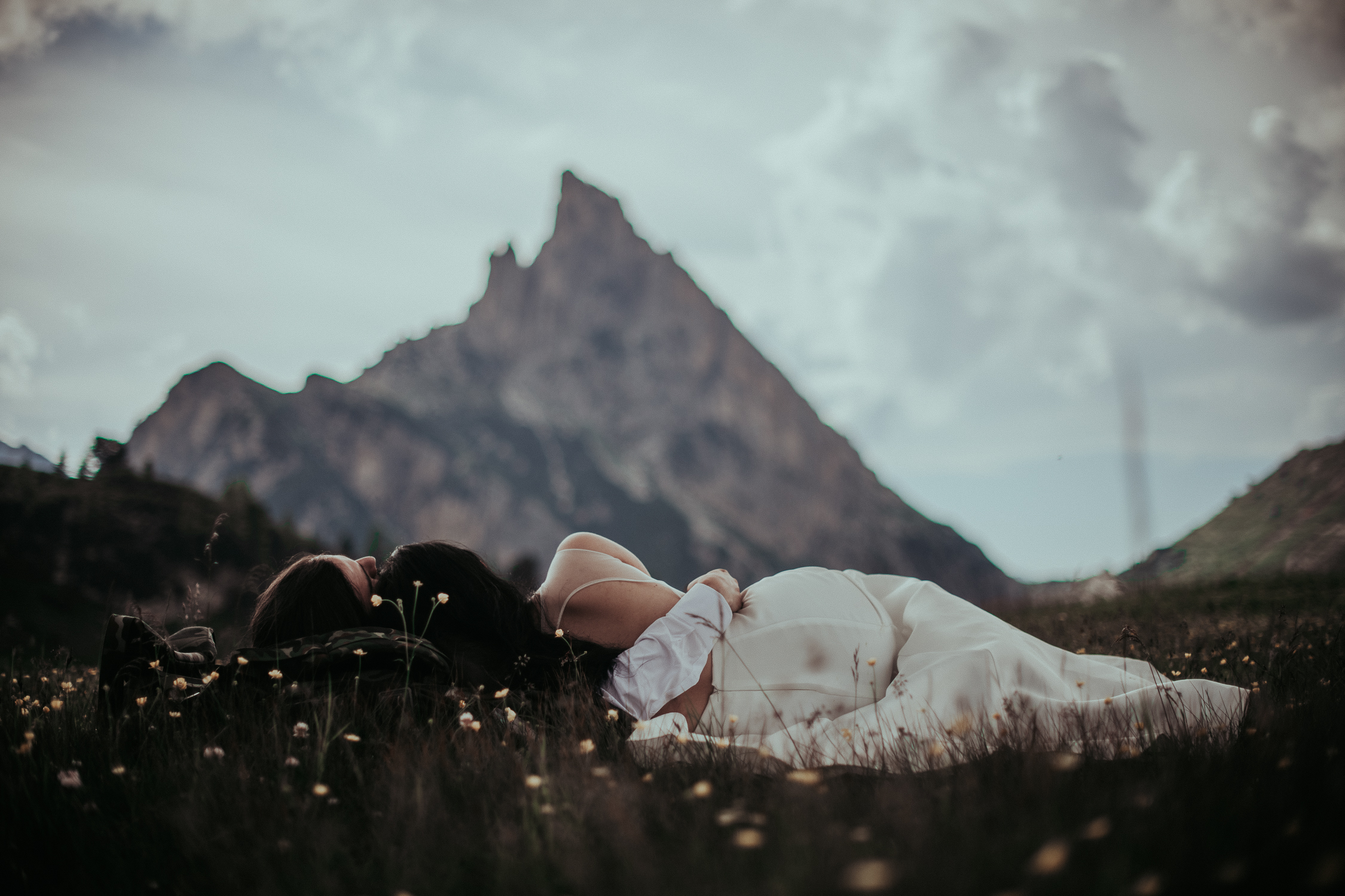 wedding couple laying in the meadows of the Dolomites
